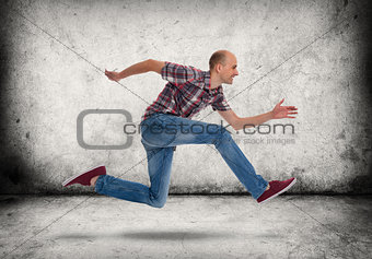 Man running. Gray concrete wall and floor