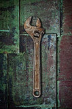 Old wrench on rusty surface.