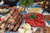 Meat and fish dishes with vegetables on the table.