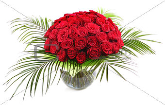 A large bouquet of red roses in a transparent glass vase. The is