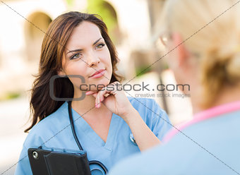 Two Young Adult Female Doctors or Nuses Talking Outside