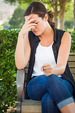 Upset Young Woman Sitting Alone on Bench