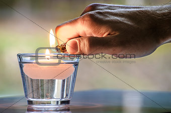 Hand with a lighter lighting a candle
