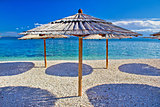 Pebble beach and turquoise sea umbrella