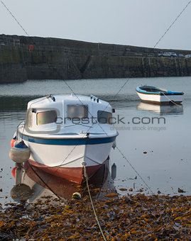 Fishing boats in harbour at sunrise long exposure image