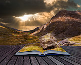 Moody dramatic mountain sunset landscape in pages of book