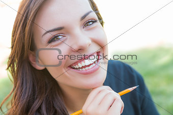 Portrait of Pretty Young Female Student with Pencil on Campus