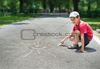 Child drawing on asphalt