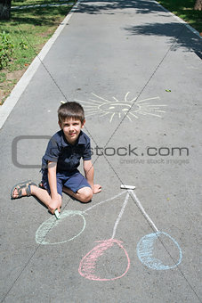 Child drawing balloons on asphalt