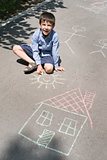 Child drawing sun and house on asphal