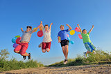 happy children jumping on field with balloons