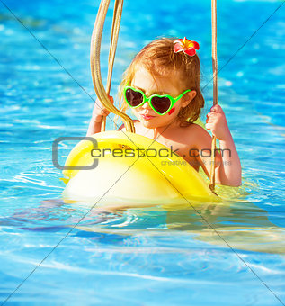 Baby girl swinging on water attractions