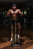 male bodybuilder using the elliptical machine