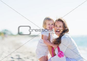 Portrait of mother and baby on sea shore