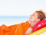 Happy young woman relaxing on sunbed