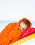 Young woman wrapped in towel laying on sunbed