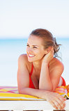 Smiling young woman on beach looking on copy space