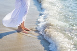 Closeup on leg of young woman standing on sea shore