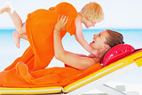 Happy mother and baby playing on chaise-longue