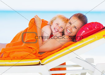 Portrait of smiling mother and baby laying on sunbed