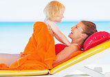 Happy mother and baby laying on sunbed