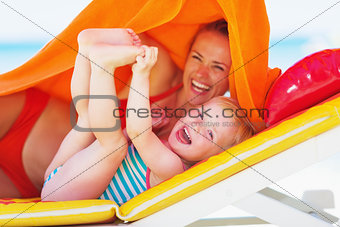 Portrait of smiling mother and baby laying on chaise-longue