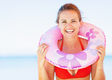 Portrait of smiling young woman on beach with swim ring