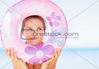Thoughtful young woman on beach looking through swim ring on cop