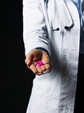 Closeup on pills in hand of doctor woman isolated on black