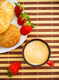 coffee, buns and strawberries on table