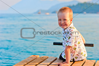 happy little boy sitting on a pier