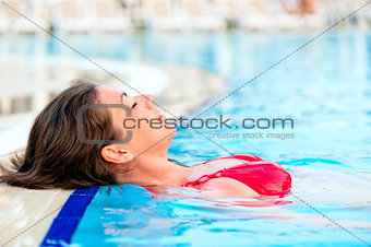 beautiful girl relaxes in the pool with your eyes closed