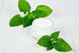 face cream in glass jar with green leaves of urtica