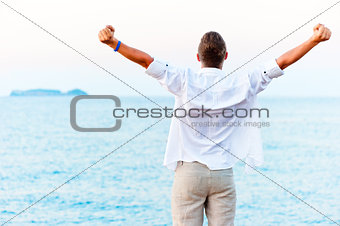 man with hands raised at the beach