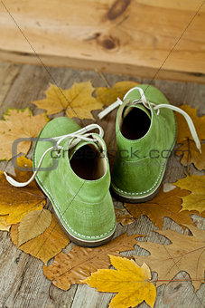 pair of green leather boots and yellow leaves