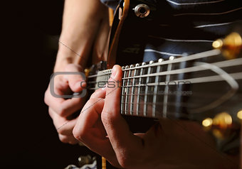 guitarist hands playing guitar over black