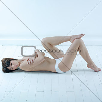 woman lying on floor topless underwear  hands hiding breast