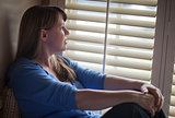 Pensive Woman Sitting Near Window Shades