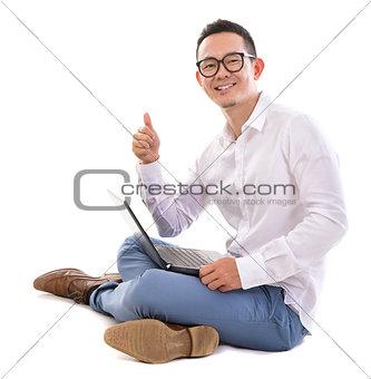 Thumb up Asian man using laptop