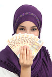 Muslim woman wearing a hijab holding a lot of money