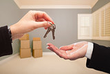 Woman Handing Over the House Keys Inside Empty Grey Room