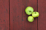 three green apples on red old wooden table
