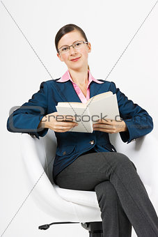 A young girl sits in a white chair with a book