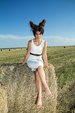 Girl in white dress and interesting hairstyle in countryside