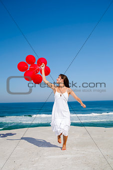 Beautiful girl running with red ballons