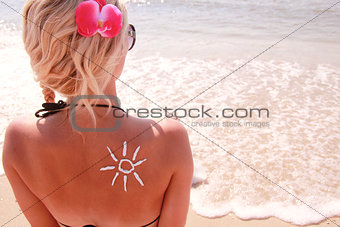 sun cream on the female back on the beach