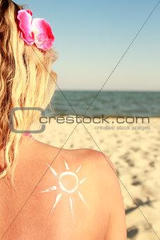 sun cream on the female back on the beach