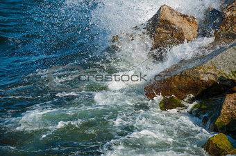 wave hitting stones