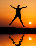 Silhouette woman jumping against orange sunset
