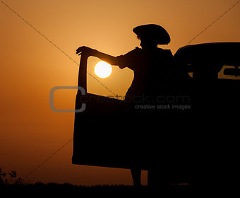 Silhouette woman with hat standing near car